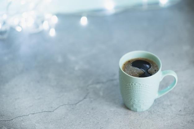Imagem creativa do chocolate quente com vara do creme e de canela em um copo cerâmico rústico azul. o conceito de férias acolhedor de inverno.