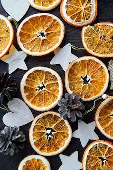 Imagem criativa de fatias de laranja secas com brinquedos de madeira em fundo preto