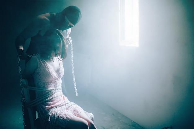 Imagem cruel do assassino em pé ao lado de uma menina morena e segurando correntes com as mãos. o pescoço da menina está amarrado com correntes. cara com máscara está olhando para ela. eles estão dentro de uma pequena sala.