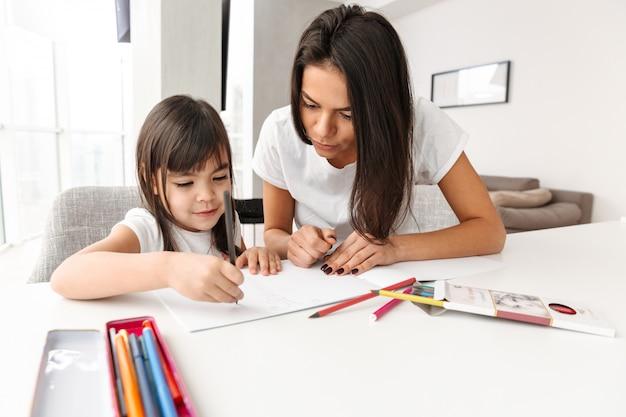 Imagem da adorável mãe e filha, aproveitando o dia juntos em casa e desenhando com marcadores e lápis