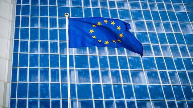 Imagem da bandeira da ue tremulando no vento contra o edifício de escritórios de negócios feito de concreto e vidro. conceito de ecenomia, desenvolvimento, governo e política