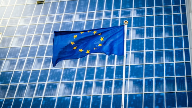 Imagem da bandeira da união europeia com estrelas sobre fundo azul contra grande edifício de escritórios moderno. conceito de ecenomia, desenvolvimento, governo e política