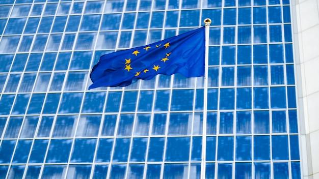 Imagem da bandeira da união europeia com estrelas sobre fundo azul contra um grande edifício de escritórios moderno