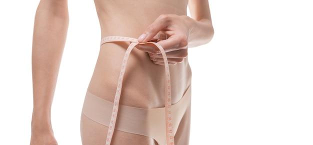 Imagem da barriga de uma mulher enrolada em uma fita centímetro. conceito médico. anti-celulite. mídia mista