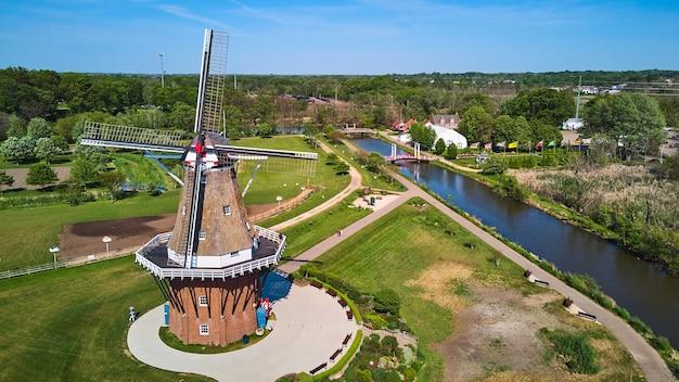 Imagem da bela antena do moinho de vento perto do rio com campos verdes