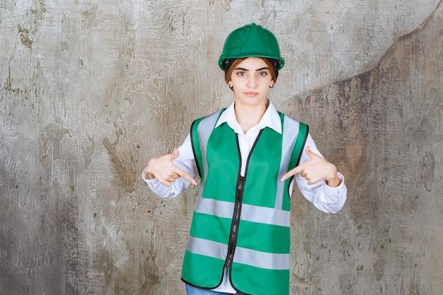 Imagem da bela arquiteta com capacete verde apontando para algo