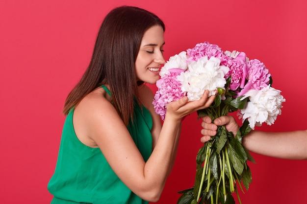 Imagem da bela morena magnética cheirando flores, fechando os olhos, sorrindo sinceramente, tendo expressão facial agradável, pessoa desconhecida, segurando peônias, isolado sobre o vermelho