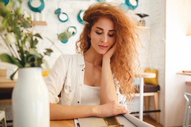 Imagem da bela ruiva jovem de pé no café enquanto lê a revista. olhando de lado.