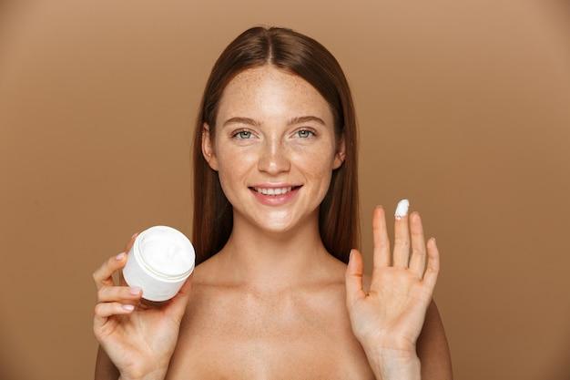 Imagem da beleza de uma jovem mulher sem camisa sorrindo e segurando um frasco com creme facial, isolado sobre um fundo bege
