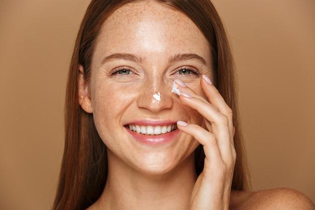 Imagem da beleza de uma linda mulher sem camisa sorrindo e aplicando creme facial, isolada sobre fundo bege