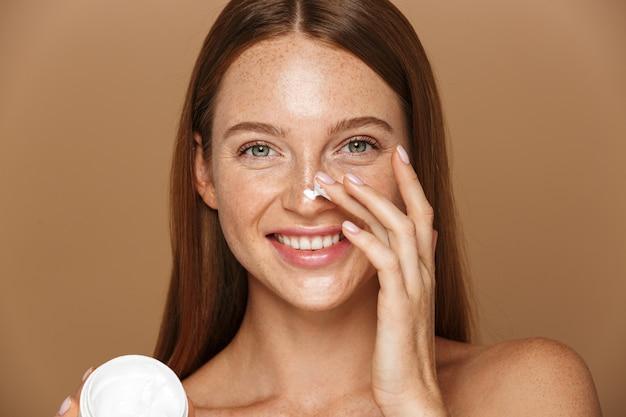 Imagem da beleza de uma mulher atraente sem camisa sorrindo e segurando o frasco com creme facial, isolado sobre um fundo bege