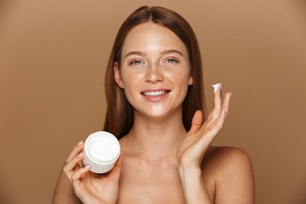 Imagem da beleza de uma mulher saudável sem camisa sorrindo e segurando um frasco com creme facial, isolado sobre um fundo bege
