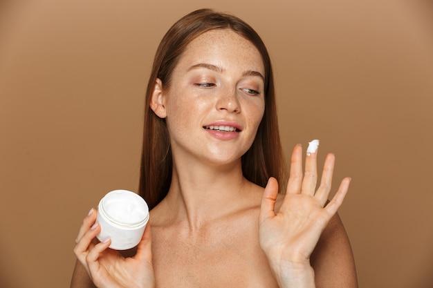 Imagem da beleza de uma mulher sem camisa satisfeita sorrindo e segurando um frasco com creme facial, isolado sobre um fundo bege