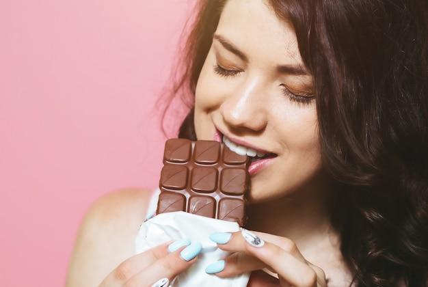 Imagem da jovem mulher bonito feliz que está isolada sobre a parede cor-de-rosa que come o chocolate.