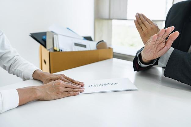Imagem da mão de uma mulher de negócios enviando uma carta de demissão ao chefe e o chefe se recusando