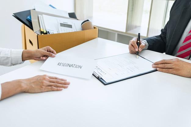 Imagem da mão de uma mulher de negócios, enviando uma carta de demissão ao seu chefe