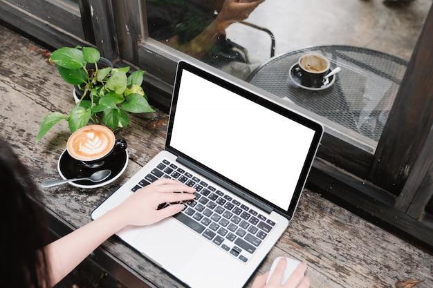 Imagem da maquete de mulher de negócios usando e digitando no laptop com tela branca em branco