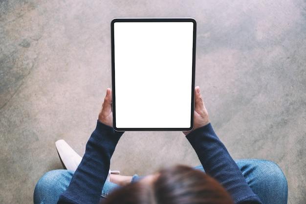 Imagem da maquete de vista superior de uma mulher segurando um tablet pc preto com uma tela em branco enquanto está sentada no chão