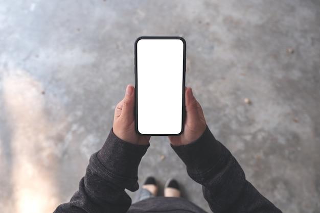 Imagem da maquete de vista superior de uma mulher segurando um telefone celular preto com uma tela em branco enquanto está de pé no chão