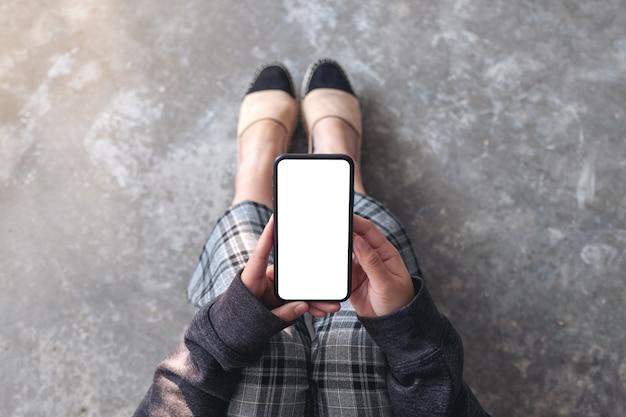 Imagem da maquete de vista superior de uma mulher segurando um telefone celular preto com uma tela em branco enquanto está sentada no chão