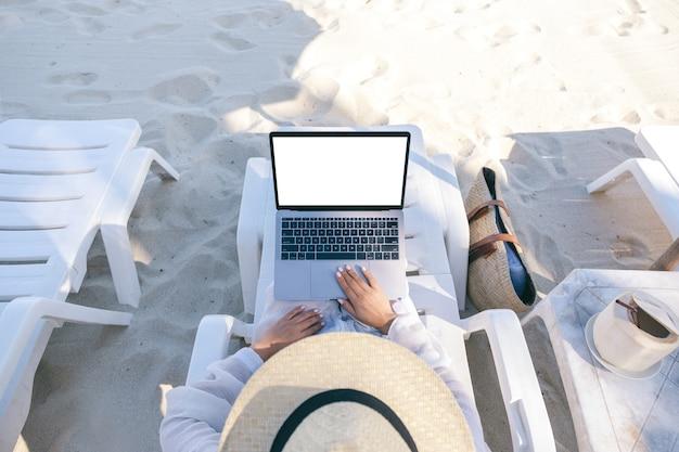 Imagem da maquete de vista superior de uma mulher usando e digitando em um laptop com uma tela em branco enquanto se deita em uma cadeira de praia na praia