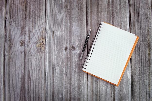 Imagem da maquete em close do livro na mesa de madeira e espaço de cópia