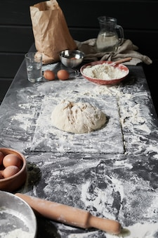 Imagem da mesa da cozinha com ovos de farinha de massa e outros ingredientes para assar