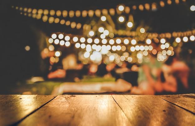 Imagem da mesa de madeira em frente ao restaurante turva abstrata luzes de fundo