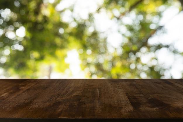Imagem da mesa de madeira na frente do fundo borrado abstrato das luzes exteriores do jardim. pode ser usado para exibir ou montar seus produtos. insira a exibição do produto