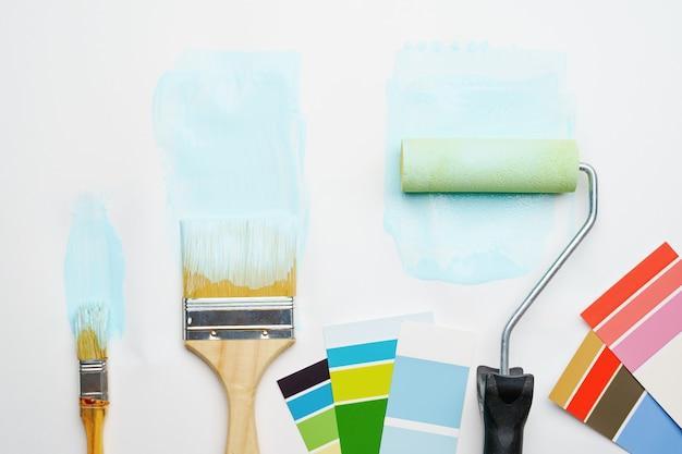 Imagem da paleta com cores azuis e verdes, rolo, pincéis em fundo branco em branco