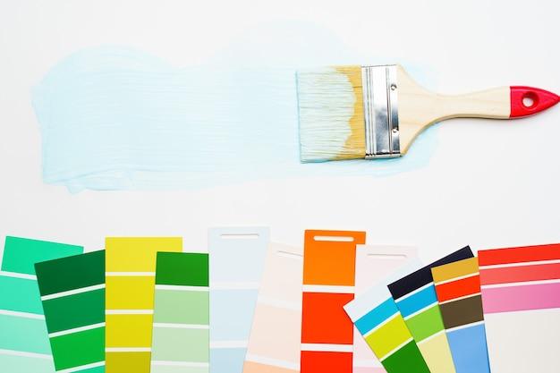 Imagem da paleta com cores azuis e verdes, vermelhas, pincel, sobre fundo branco em branco ... lugar para texto.