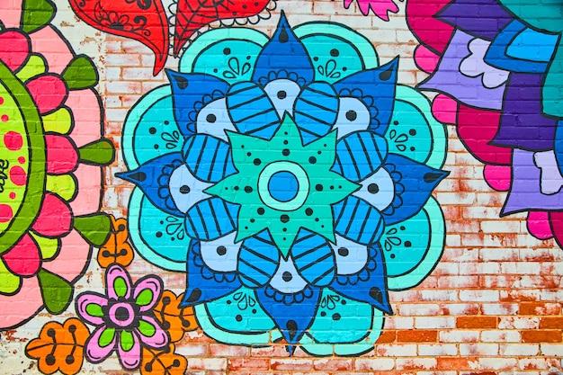 Imagem da parede de tijolos com um mural de padrões de flores coloridas