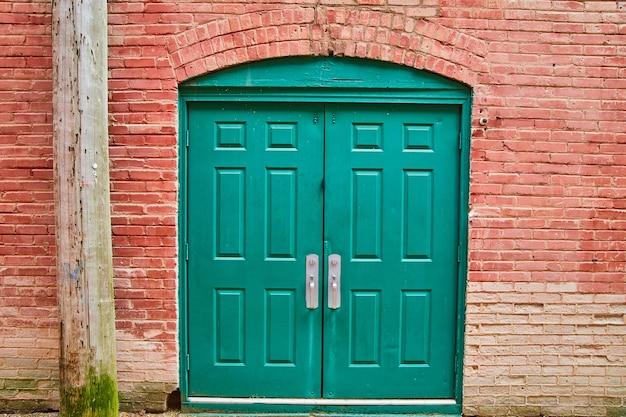 Imagem da porta dupla verde do beco com tijolo vermelho