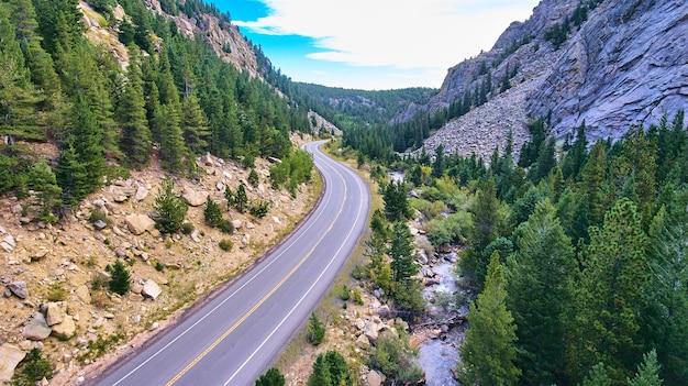 Imagem da rodovia ao lado do rio em um desfiladeiro cercado por montanhas e pinheiros