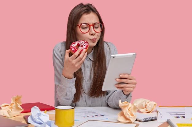 Imagem da senhora bonita séria segurando um donut delicioso, assiste ao vídeo de treinamento no touchpad, prepara o relatório de negócios, analisa o gráfico