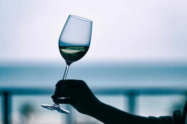 Imagem da silhueta da mão de uma mulher segurando uma taça de vinho com o fundo do mar desfocado