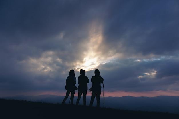 Imagem da silhueta de três mulheres em pé, observando o pôr do sol com a vista das montanhas ao anoitecer