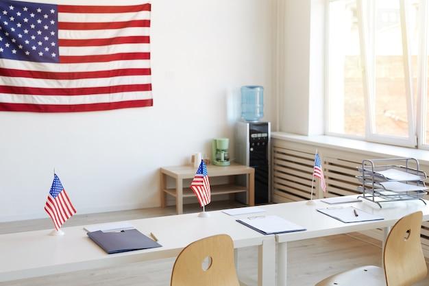 Imagem da superfície de uma assembleia de voto vazia decorada com bandeiras americanas no dia das eleições, copie o espaço