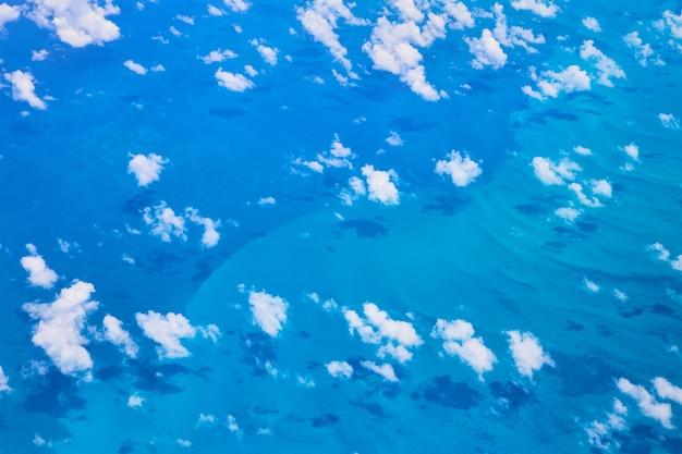 Imagem da vista de um avião de nuvens projetando sombras contra a água do oceano