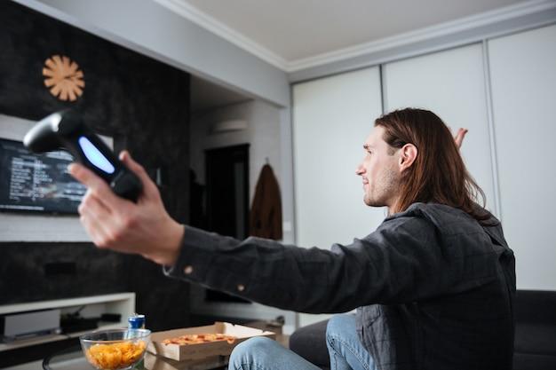 Imagem da vista lateral do jogador jovem triste sentado em casa