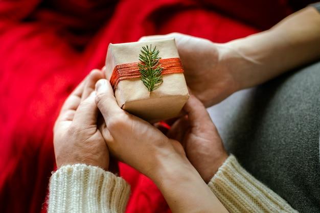Imagem da vista superior da mão masculina e fêmea com caixa de presente. conceito de celebração familiar de natal e ano novo.
