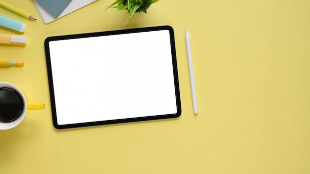 Imagem da vista superior da mesa de trabalho colorida com acessórios colocando sobre ela. plano colocar tablet computador com tela em branco branca, caneta, caneta, caderno, diário, xícara de café e planta em vaso.