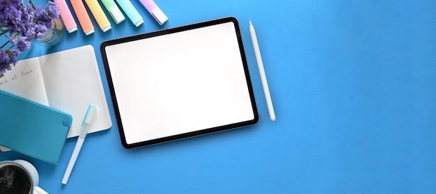 Imagem da vista superior da tabuleta branca do computador da tela em branco que põe sobre a mesa de trabalho colorida com caneta, nota, canetas, copo de café e flores em um vaso de vidro. conceito de espaço de trabalho colorido ordenado.
