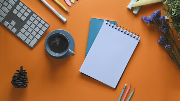 Imagem da vista superior da xícara de café, colocando sobre a mesa de trabalho colorida, rodeada por teclado de computador, nota, lápis, caneta, pinha de flores e canetas. conceito de espaço de trabalho desordenado.