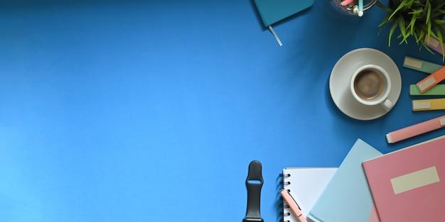 Imagem da vista superior da xícara de café quente branca, colocando sobre a mesa de trabalho colorida, cercada por canetas, cadernos, smartwatch, nota, porta-lápis e vaso de plantas. conceito de espaço de trabalho desordenado.