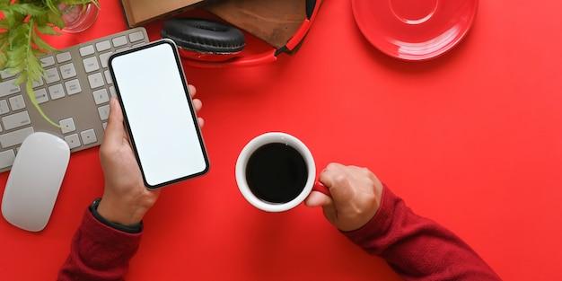 Imagem da vista superior das mãos segurando um smartphone de tela em branco branco e uma xícara de café quente sobre o teclado sem fio que rodeado por livros antigos, fone de ouvido, mouse sobre a mesa de trabalho colorida.