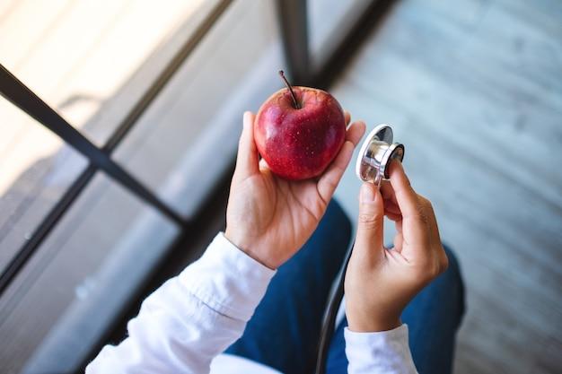 Imagem da vista superior de um médico usando um estetoscópio para examinar uma maçã vermelha