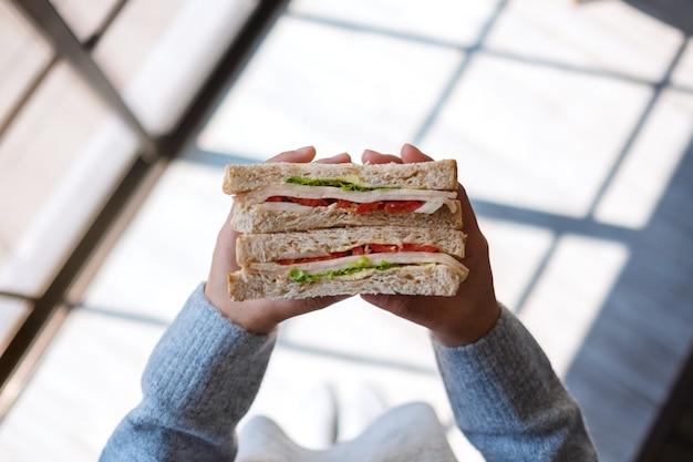 Imagem da vista superior de uma mulher segurando e comendo um sanduíche de trigo integral pela manhã