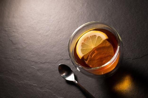 Imagem da vista superior de uma xícara de chá com limão em fundo de granito preto