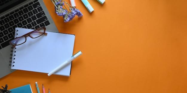 Imagem da vista superior do computador portátil, colocando sobre a mesa de trabalho colorida, rodeada de caderno, óculos, caneta, flores, canetas e lápis. conceito de espaço de trabalho ordenado.